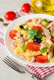 Fusilli pasta salad with tuna, tomatoes, black olives and basil on gray stone background. Selective focus stock image