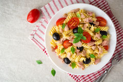 Fusilli pasta salad with tuna, tomatoes, black olives and basil on gray stone background. Top view stock photography