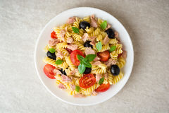 Fusilli pasta salad with tuna, tomatoes, black olives and basil on gray stone background. Top view royalty free stock photo