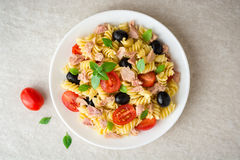 Fusilli pasta salad with tuna, tomatoes, black olives and basil on gray stone background. Top view royalty free stock image