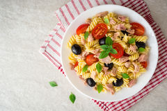Fusilli pasta salad with tuna, tomatoes, black olives and basil on gray stone background. Top view royalty free stock photos