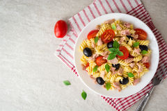 Fusilli pasta salad with tuna, tomatoes, black olives and basil on gray stone background. Top view stock images