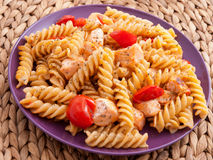 Fusilli pasta with salmon. And cherry tomatoes in a purple plate royalty free stock photos