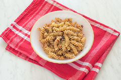 Fusilli pasta. With spice on a plate stock images