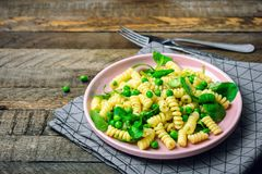 Fusilli pasta. With spinach and green peas stock photos