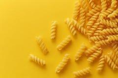 Fusilli pasta spirals. On yellow background royalty free stock photo