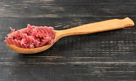 Fusilli pasta in spoon. Red raw fusilli pasta in spoon on wooden background royalty free stock photo
