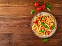 Fusilli pasta with tomato sauce, chicken fillet with basil leaves on dark brown wooden background, copy space, top view.  stock image