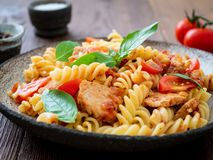 Fusilli pasta with tomato sauce, chicken fillet with basil leaves on dark brown wooden background, cope space, side view.  stock photo