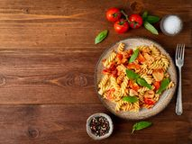 Fusilli pasta with tomato sauce, chicken fillet with basil leaves on dark brown wooden background, copy space, top view.  royalty free stock image