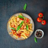 Fusilli pasta with tomato sauce, chicken fillet with basil leaves on dark stone concrete background, top view.  stock images