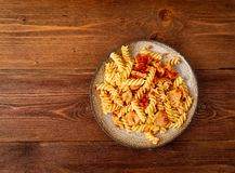 Fusilli pasta with tomato sauce, chicken fillet on dark brown wooden background, copy space, top view.  royalty free stock images