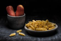 Fusilli pasta and tomatoes dark food style Royalty Free Stock Image