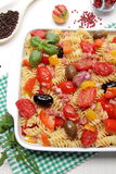 Fusilli pasta with tomatoes, olives and peppers Stock Photos