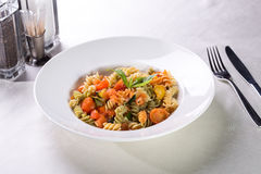 Fusilli pasta. With tomatoes and zucchini served on the table Royalty Free Stock Photography