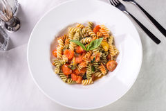 Fusilli pasta. With tomatoes and zucchini served on the table Stock Photography
