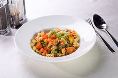 Fusilli pasta. With tomatoes and zucchini served on the table Royalty Free Stock Photos