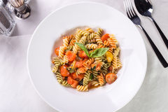 Fusilli pasta. With tomatoes and zucchini served on the table Royalty Free Stock Image