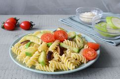 Fusilli Pasta with tomatos and grilled Zucchini, Eggplant. Vegeterian lunch on grey wooden background royalty free stock photography