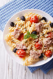 Fusilli pasta with tuna, tomatoes and parmesan closeup. vertical. Fusilli pasta with tuna, tomatoes and parmesan close-up on the table. vertical top view Stock Photos