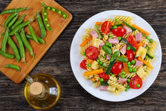 Fusilli pasta with vegetables and ham. Fusilli pasta with carrot and zucchini sticks, ham, emmental cheese, green peas, cherry tomatoes on white plate on wooden stock photography