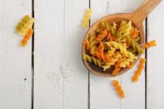 Fusilli pasta. Wooden ladle with colorful fusilli pasta stock images