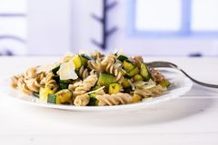 Fusilli pasta with zucchini with blue window stock image