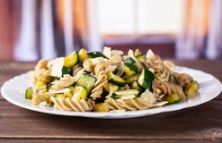 Fusilli pasta with zucchini with curtains stock image