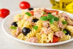 Fusilli pastasallad med tonfisk, tomater, svarta oliv och basilika på grå färger stenar bakgrund Royaltyfri Fotografi