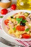 Fusilli pastasallad med tonfisk, tomater, svarta oliv och basilika på grå färger stenar bakgrund Royaltyfria Foton