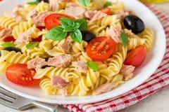 Fusilli pastasallad med tonfisk, tomater, svarta oliv och basilika på grå färger stenar bakgrund Arkivfoton
