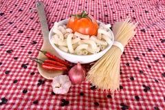 Fusilli, spaghetti, macaroniknoflook, en sjalotten op stof Royalty-vrije Stock Afbeeldingen