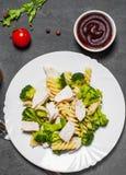 Fusilli-Teigwaren mit Hühnerbrust- und Brokkolisalat in der weißen Platte stockfotos