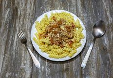 Fusilli with tuna and cheese on the wooden background. Homemade pasta with tomato, cheese and herbs. Basil, oregano and pepper. Healthy dinner with seafood stock images