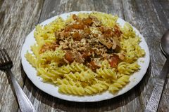 Fusilli with tuna and cheese on the wooden background. Homemade pasta with tomato, cheese and herbs. Basil, oregano and pepper. Healthy dinner with seafood stock photo