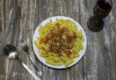 Fusilli with tuna and cheese on the wooden background. Homemade pasta with tomato, cheese and herbs. Healthy dinner with seafood. Fork and spoon near the plate stock images