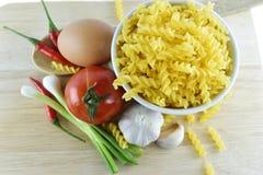 Fusilli, vitlök, chili, lök, ägg och tomat på trä Royaltyfri Fotografi