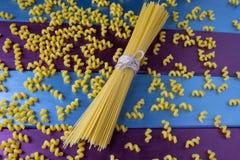Fusilly-Teigwaren und ein Bündel Spaghettis am hellen bunten Hintergrund stockfotos