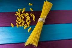 Fusilly-Teigwaren und ein Bündel Spaghettis am hellen bunten Hintergrund stockbilder