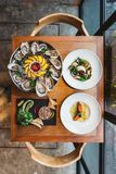 Fusion fine dining meal: Many kinds of Fresh Oyster, Ravioli in cream sauce with Grilled Salmon, Smoked Galician Octopus. Fusion fine dining meal: Many kinds of royalty free stock photography