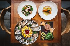 Fusion fine dining meal: Many kinds of Fresh Oyster, Ravioli in cream sauce with Grilled Salmon, Smoked Galician Octopus. Fusion fine dining meal: Many kinds of stock photo