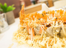 Fusion food 1. Sushi roll with deep fried shrimp and imitation crab stick at the restaurant (Japanese food, fusion food style), selective focus royalty free stock image