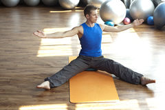 Fusion of mind and body - man practicing pilates. In light gym royalty free stock images