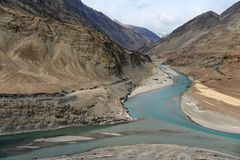 Fusione delle alte montagne dei fiumi di Zanskar e di Indus: due correnti del turchese si fondono in un fiume fra le alte scoglie Fotografia Stock Libera da Diritti