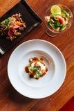 Fusionsnahrung: Rindfleischburger Canape, der mit Ei übersteigt, pochieren, Tomate und Koriander stockbild