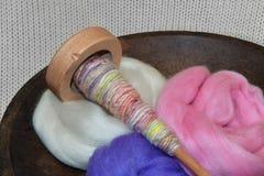 Fuso di legno con il filato della mano in una ciotola di legno di vagabondaggio della lana Fotografia Stock
