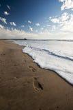 Fuss-Drucke im Sand mit Pier im Hintergrund Stockfoto