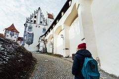 FUSSEN, GERMANY - DECEMBER 2018: woman standing at the entrance of Hohes castle.  royalty free stock image