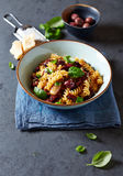 Fussili pasta with olives, capers, dried tomatoes and parmesan Royalty Free Stock Image