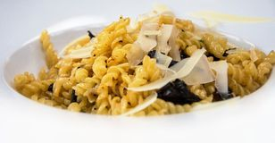Fussili pasta. Pasta fussili with parmesan chips and olives on white plate Royalty Free Stock Photography